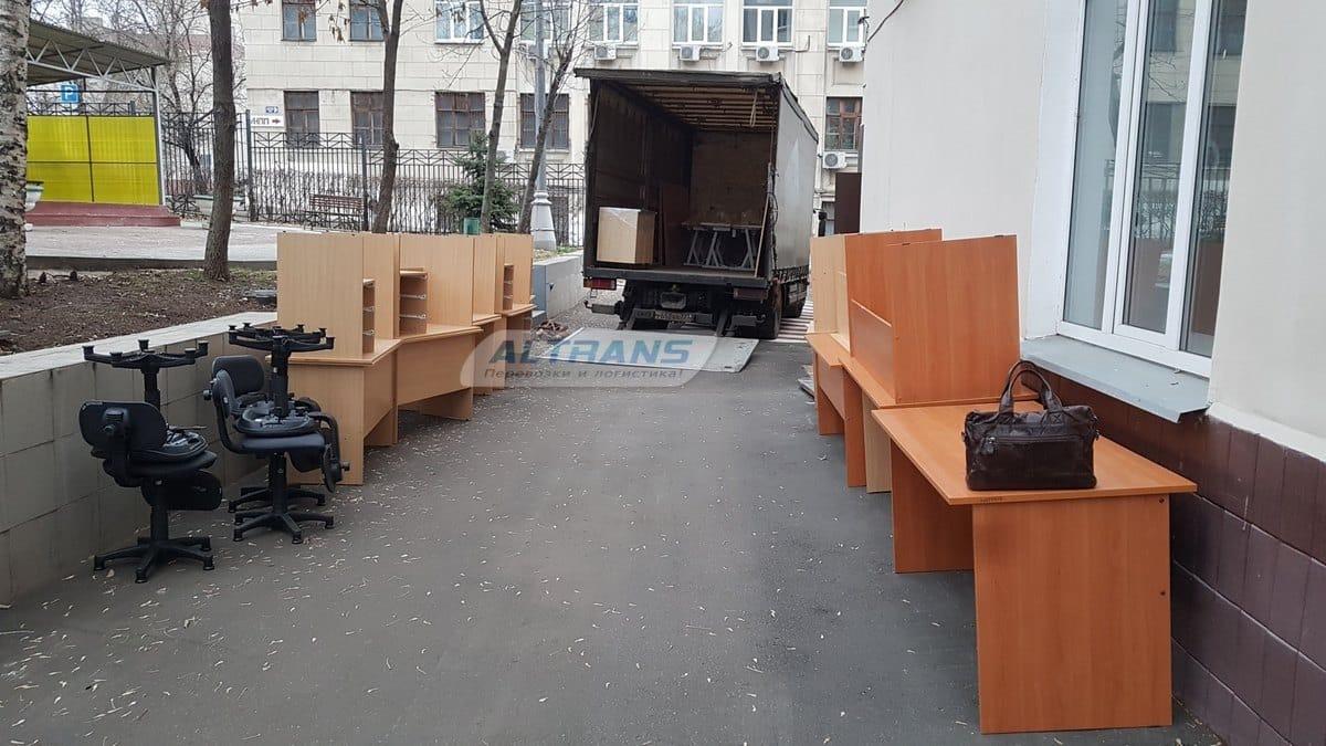 Погрузка офисных столов и кресел в грузовик
